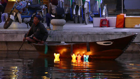 Guy at a small boat on thu bon river with Floating lanterns in the water Footage