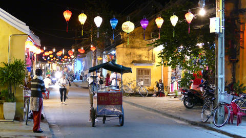 Vietnamese lady walks with a cart through a street with Colorful lanterns in Hoi Footage