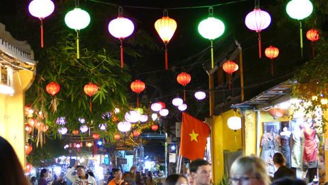 Tourists in a street with Colorful lanterns and the Vietnamese flag in the old t Footage