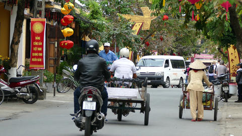 Elderly lady pushing a cart to collect goods in the old town of Hoi An Footage
