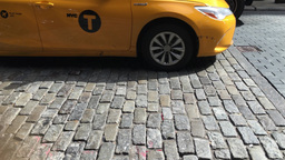 Cars and yellow taxi cabs driving cobblestone in Soho, Manhattan Footage