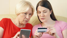 Mother and daughter shopping online with credit card on smartphone. Technology Footage