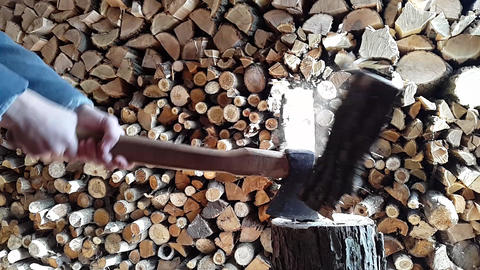 Man chopping wood with an ax on background a pile of firewood Slow motion 画像