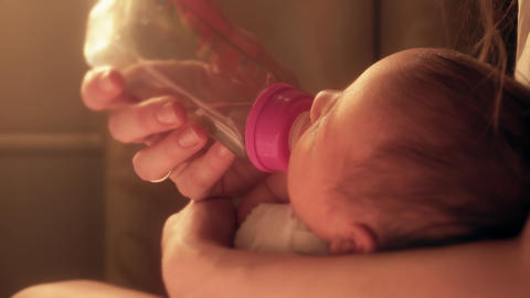 Newborn baby girl drinks from the bottle nipple in her mom's hands Footage
