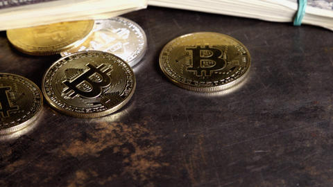 Coins of bitcoin on banknotes of one hundred dollars bills in batches spins on Footage