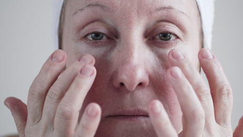 Caucasian mid age woman applying cream to her face Footage
