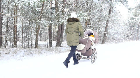 woman with baby carriage walking in a snowy winter park ビデオ