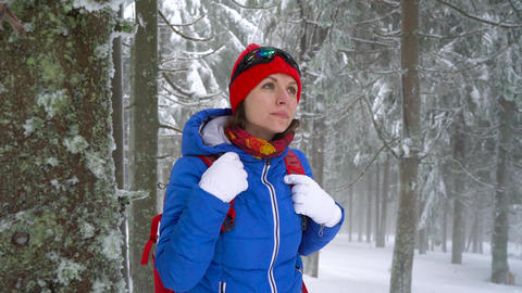 Lonely tourist girl walking on a winter snow-covered coniferous forest in the Footage