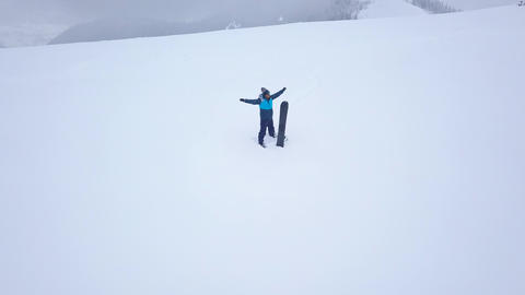 Flight over the man with a snowboard which stands on top of a snow-capped Footage