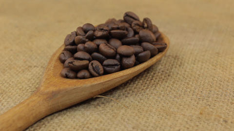Close-up, spoon rotation with a pile of coffee beans lying on burlap Footage