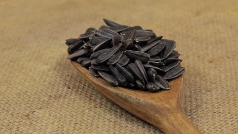 Close-up, spoon rotation with a pile of sunflower seeds lying on burlap Footage