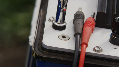 Person Hand Plugs in Isolated Cords into Equipment Footage