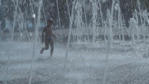 The boy runs through the fountain Footage