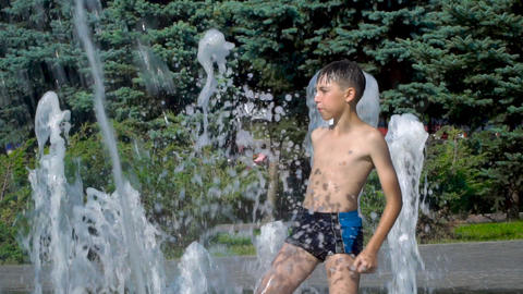 The boy is playing in the fountain Footage