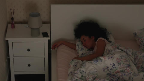 Girl is sleeping on the bed at night Top view Live Action