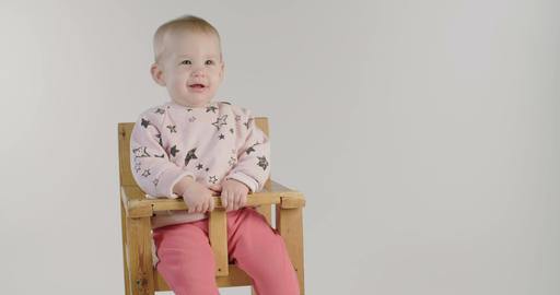 Cute baby smiling on a white studio background GIF