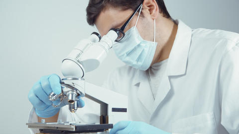 Scientist in uniform looking at microscope Footage