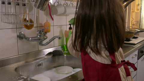 Young girl washing dishes no face Footage