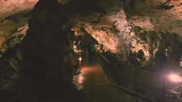 Group of adult tourists exploring the Saeva Cave in Bulgaria Footage