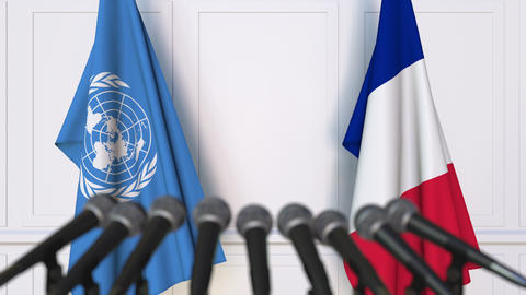 Flags of the United Nations and France at international meeting or negotiations Footage