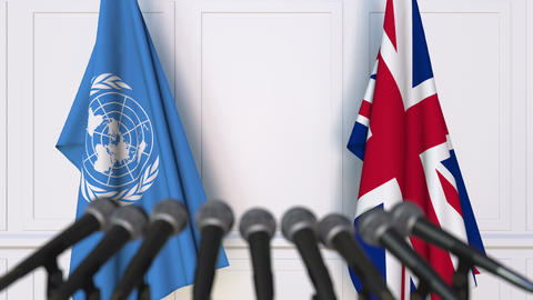 Flags of the United Nations and The United Kingdom at international meeting or Live Action