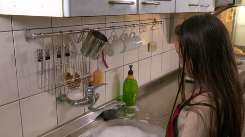 Young girl washing dishes tilt down high- Footage