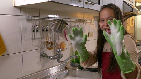 Young girl washing dishes showing foamy hands Footage