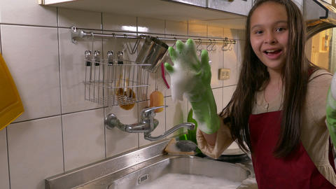 Happy young girl washing dishes showing foamy hands Footage