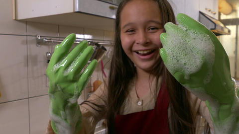 Happy young girl washing dishes showing foamy hands laughing Footage