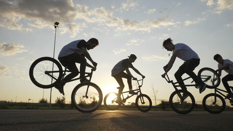 Cool young bikers team doing freestyle front wheelie trick outside with sunset Footage