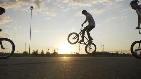 Acrobat young bikers squad doing ollie hop tricks on bikes with summer sunset in Footage