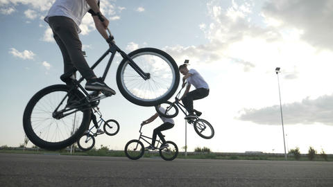 Four professional bicyclers performing an entertaining show practicing jumps and Footage