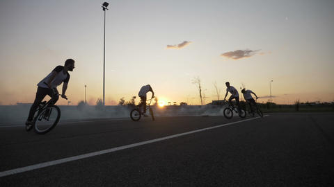 Group of passionate bikers performing various tricks on bicycles smoke coming Live Action