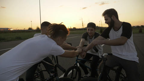 Team of boys with bikes expressing team building success touching their hands Footage