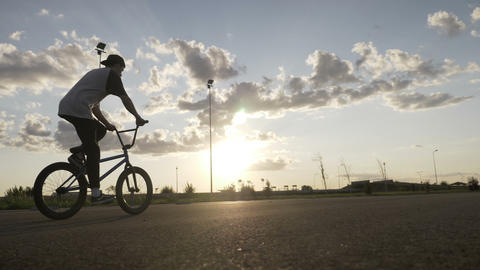 Sportive teenager relaxing on bike riding and doing tricks with sunset in Live Action