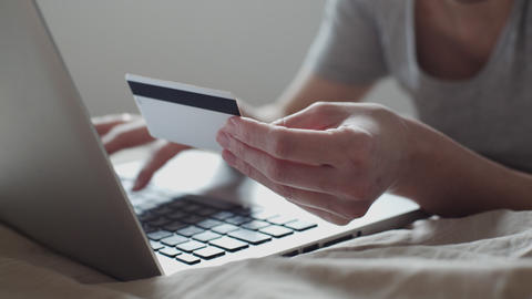 Girl in bed shopping online with credit card Footage