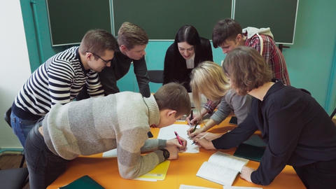 Young students with a teacher writing and discussing something in classroom Footage