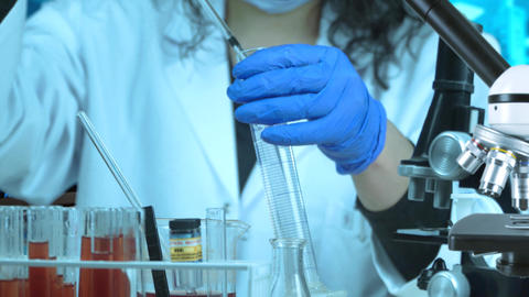 Woman researcher working in lab. Female researcher writing research report in Live Action