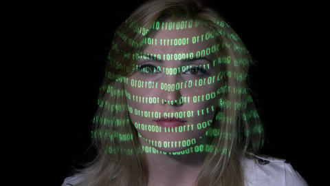 Green binary code projected on the face of an sexy smart software developer Footage
