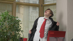 Young man in a suit dances in the office, makes funny faces, fools around Footage