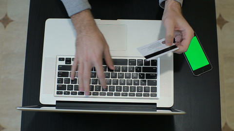 A man paying for online shopping using laptop and credit card. This image is ill Footage