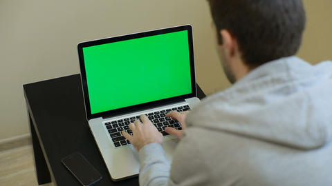 A man types on a laptop. Young Handsome Man Sits and Works on Green Screen Lapto Footage