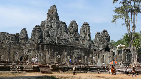 Monk and other tourists walking towards the Bayon Khmer temple Footage