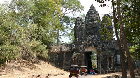 Tuk Tuks drives with tourists through one of the gates at Angkot Wat Footage