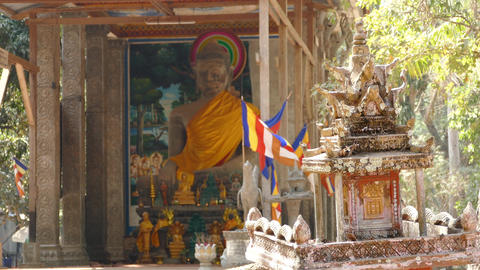 Spirit House In Front Of A Temple With A Big Buddha And Flags In Angkor Wat stock footage