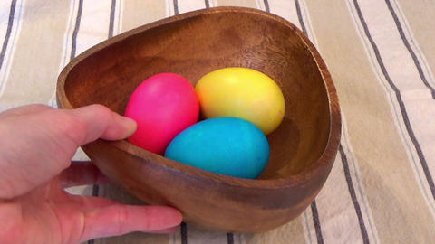 Hand placing Easter painted eggs in a wooden bowl on the table ビデオ