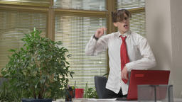Young man in a suit dances in the office,takes off his jacket, makes funny faces Footage