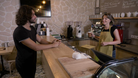Cheerful happy positive female seller serving a charismatic customer with a Footage
