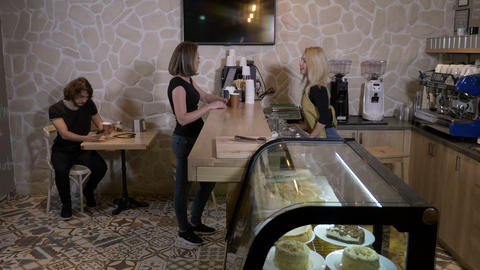 Cheerful young blonde barista worker serving coffee to go to a female client in Live Action