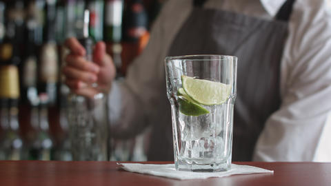 Bartender preparing cocktail with ice and lime Footage